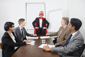 Business leader as superhero in front of colleagues — Stock Photo