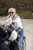 Senior woman on motorcycle in desert — Stock Photo