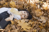 Woman lying on leaves — Stock Photo
