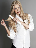 Blonde girl with hair straightener — Stock Photo