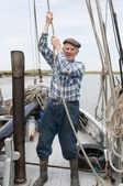 Elderly fisherman pulling rope on deck — Stock Photo
