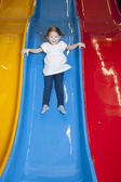Girl slides down colorful slide — Stock Photo