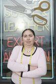 Woman standing infront of laundrette shop window — Stock Photo