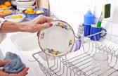 Senior woman arranging plate in rack — Stock Photo