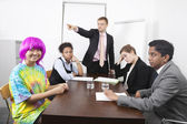Businesspeople with colleague in pink wig — Stock Photo