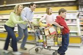 Family run with full shopping trolley — Stock Photo
