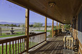Ranch porch overlooking horse stables — Stock Photo