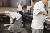 Three chefs work together in busy kitchen — Stock Photo