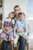 Children sitting on father's laps — Stock Photo