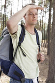 Man  shielding eyes in forest — Stock Photo