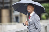 African American businessman with umbrella — Stock fotografie