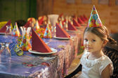 Girl seated at birthday table — Stock Photo