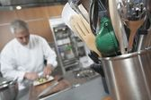 Mid- adult chef working with utensil holder in foreground — Stock Photo