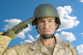 Soldier in military uniform saluting — Stock Photo