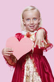 Girl dressed in princess costume holding paper heart — Stock Photo