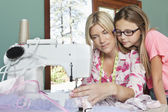 Girl looking at mother sewing cloth — Stock Photo