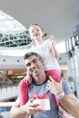Daughter sits on fathers shoulders — Stock Photo