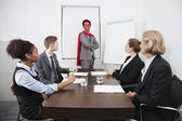 Business leader superhero in front of colleagues — Stock Photo
