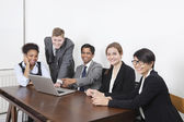 Multiethnic professionals using laptop — Stock Photo
