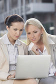 Businesswomen working on laptop together — Stock Photo