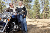 Senior couple lean on motorcycle in forest — Stock Photo