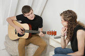 Young man strumming guitar — Stock Photo