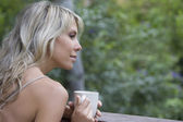 Blonde woman sits with cup on garden veranda — Stock Photo