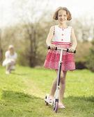 Girl riding scooter through park — Stock Photo