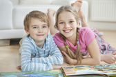 Happy brother and sister with story books — Stock Photo