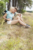 Couple relaxing while hiking in forest — Stock Photo