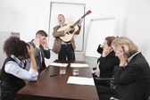 Businessman playing guitar in meeting — Stock Photo