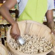 Clerk with basket of peanuts — Stock Photo #34020375