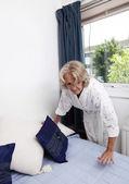 Senior woman arranging cushions — Stock Photo