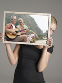 Businesswoman peeking from behind photograph — Stock Photo