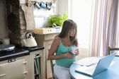 Pregnant woman sitting at kitchen table with laptop — Stock Photo