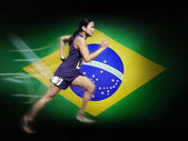 Woman running in front of Brazilian Flag — Stock Photo