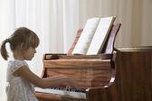 Girl playing piano — Stock Photo