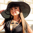 Attractive young lady in a black hat — Stockfoto