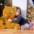 Cute little girl hugging a huge bear near the Christmas tree and fireplace — ストック写真