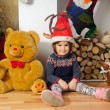Little cute girl sitting near the Christmas tree and decorated fireplace with a huge bear — Stock Photo #34230777