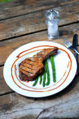 Grilled porkchop on the bone served with asparagus — Stock Photo