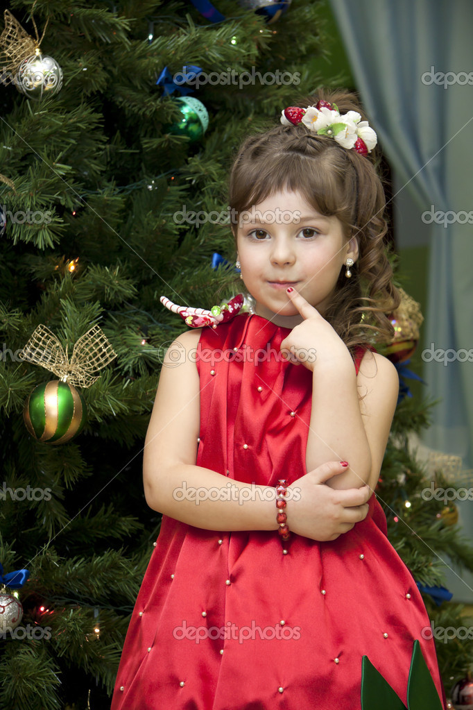 Little girl in the strawberry dress costs near the decorated fur-tree and waits for a gift  Stock Photo #13201307