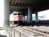 Train moves along tracks under highway — Stock Photo