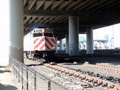 Treno che si muove lungo tracce sotto autostrada — Foto Stock