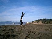Man Handstands on Ocean Beach — Stock Photo