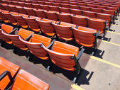 Rows of empty orange stadium seats — Stok fotoğraf