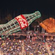 Fans sitting in bleacher section with large glove and giant Coca — ストック写真