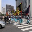 Line of dressed in traditional Korean outfits carry flags — Stock Photo