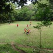 Native Costa Ricans Play Soccer on a field in the Woods - Stock Photo