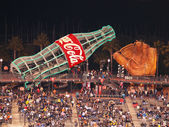 Fans sitting in bleacher section with large glove and giant Coca — Stockfoto